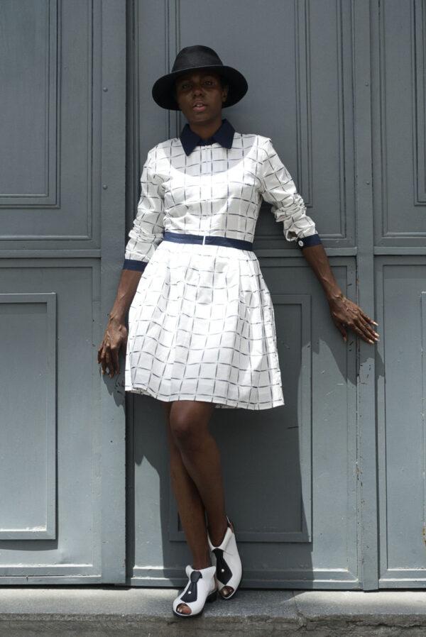 Black young female model in Vaandom's Dyzed dress wearing a black fedora in front of wooden grey door.
