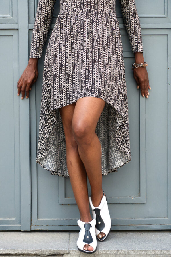 Close-up of black young female's legs in Vaandom's Hilo dress in front of wooden grey door. She's wearing black and white high heels and silver statement bracelet.