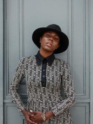 Close-up of black young female model in Vaandom's Hilo dress wearing a black fedora hat in front of wooden grey door.