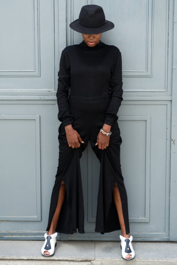 Black young female model posing in Vaandom's Smexxed dress in front of wooden grey door. She's wearing a black fedora, a silver statement bracelet on her left wrist and black and white high heels..