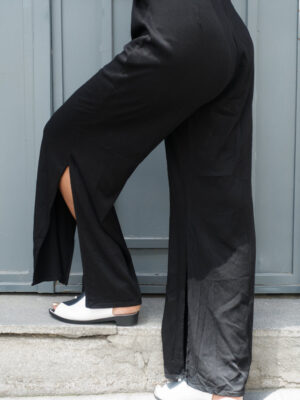Close-up of black young female model's legs in Vaandom's Smexxed dress in front of wooden grey door. She's wearing black and white high heels.