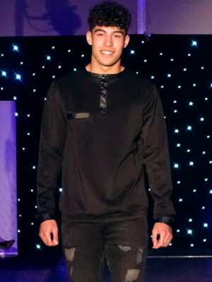Close-up of young male model on a catwalk wearing black Styler jumper. Front shot.