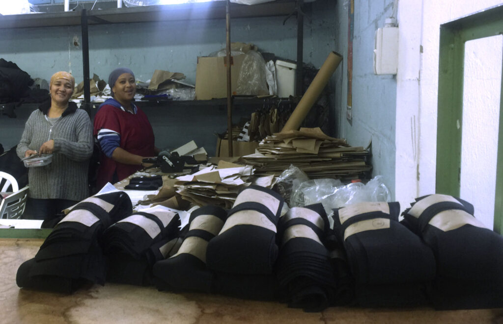 Vaandom's workshop in Cape Town. Two women smile to the camera behind a table with several stacks of clothes. Behind them there is a big shef storing boxes and pieces of fabric.